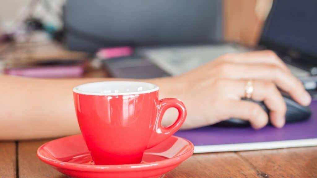 Kaffeeunverträglichkeit - rote Tasse Kaffee vor dem Laptop