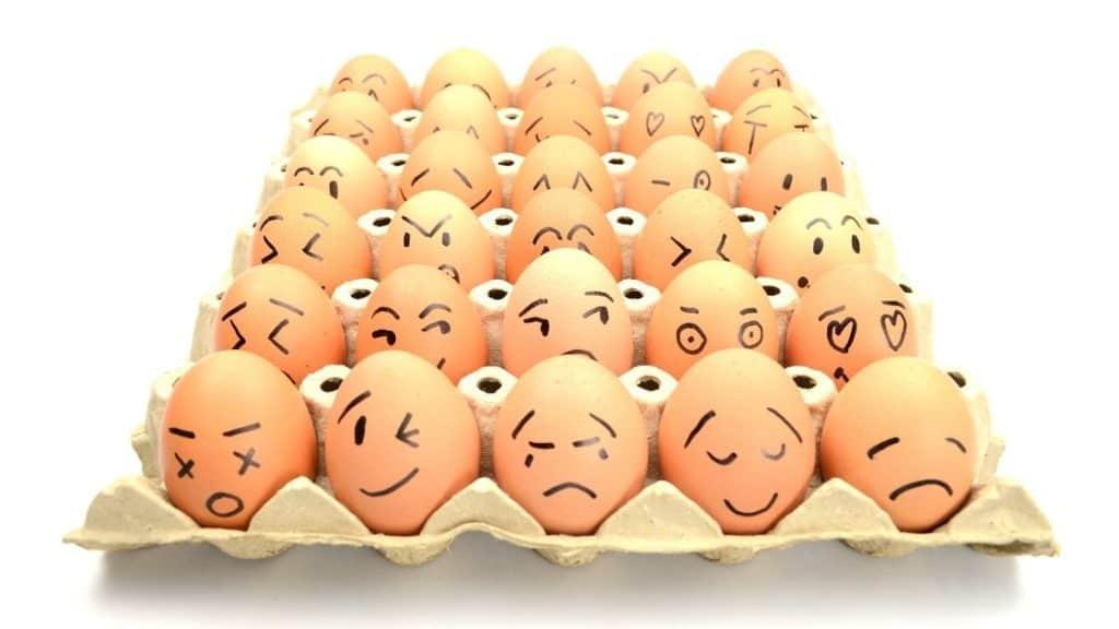 Mehrere Eier in einem Eierkarton mit aufgemalten Gesichtern