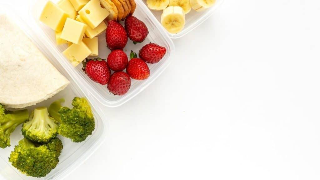 Verschiedene Lebensmittel in Boxen - Brokkoli, Erdbeeren, Banane, Käse